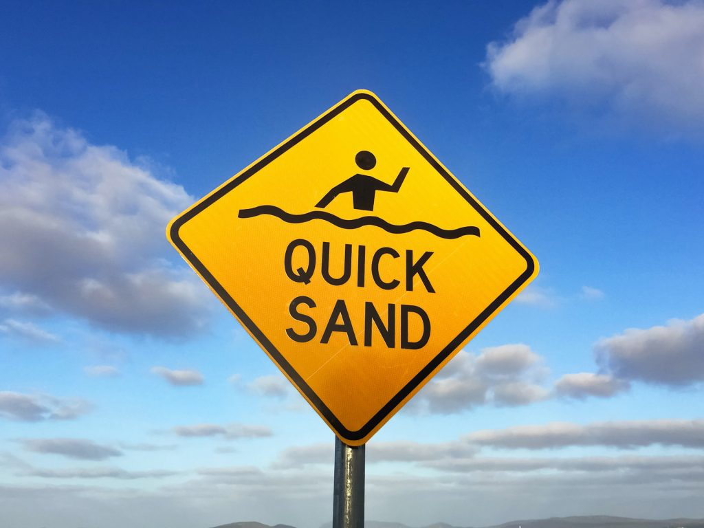 Yellow caution sign with text: Quick Sands